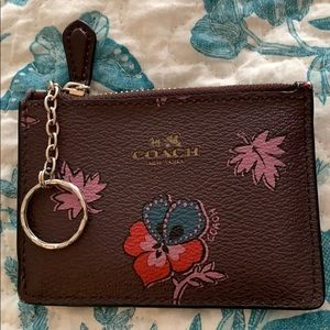 A small coach wallet with flower like designs.